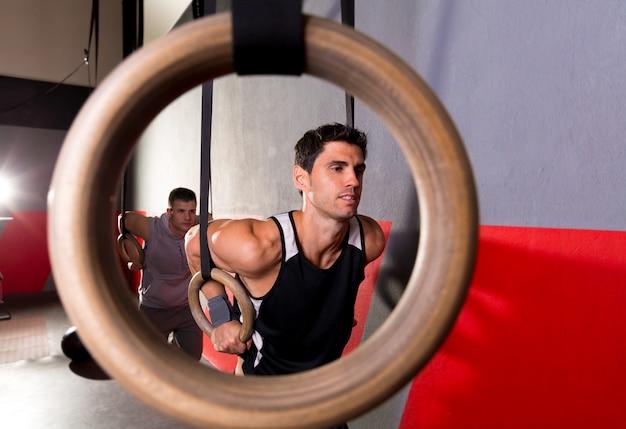 Homem de treino de anéis de mergulho de um buraco de anel no ginásio