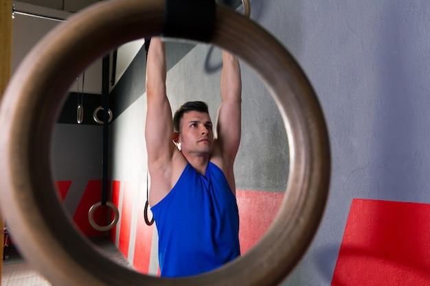 Homem de treino de anéis no ginásio pendurado