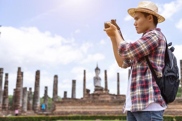 Homem de turista asiático no parque histórico de sukhothai, tailândia