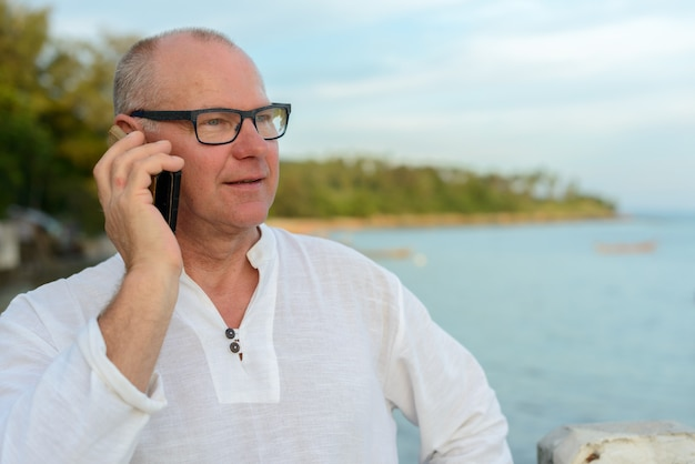 Homem de turista bonito maduro feliz falando ao telefone contra a vista da praia ao ar livre