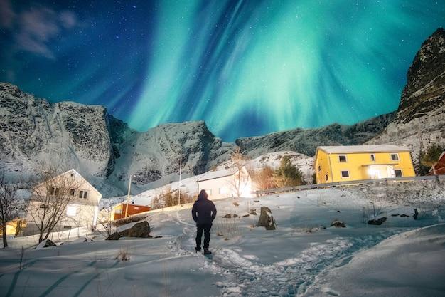Homem de turista em pé com olhando para aurora boreal no céu em nevado na vila de pescadores