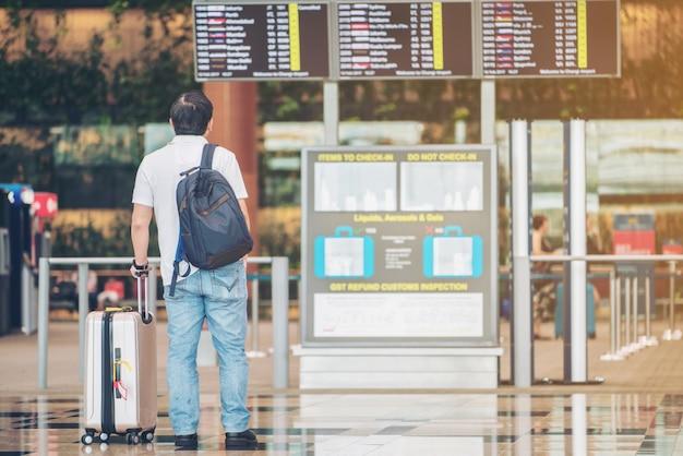 Homem de turista, olhando para o quadro de informações de voo no aeroporto