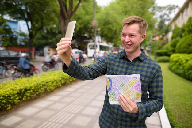 Homem de turista, segurando o mapa e tirar selfie com o telemóvel