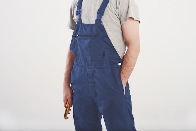 Homem de uniforme azul em pé contra a parede branca do estúdio