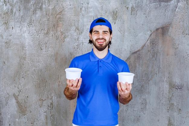 Homem de uniforme azul segurando dois copos de plástico para viagem com as duas mãos.