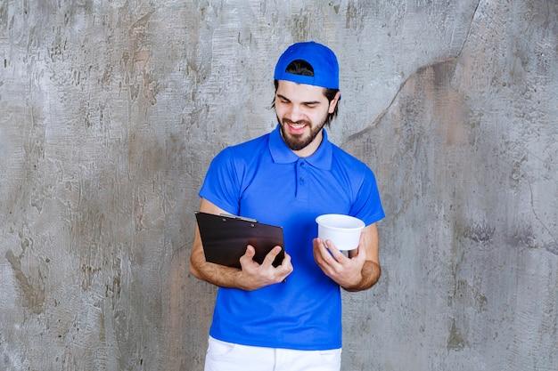 Homem de uniforme azul segurando um copo de plástico para viagem e lendo o nome do cliente.