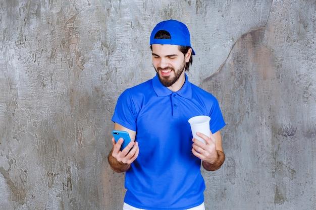Homem de uniforme azul segurando uma bebida para viagem e fazendo uma videochamada.