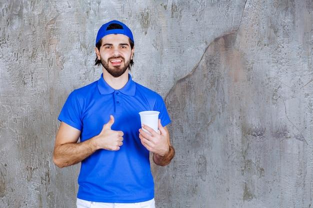 Homem de uniforme azul segurando uma bebida para viagem e mostrando um sinal positivo com a mão.