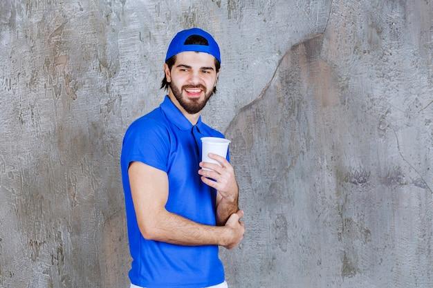 Homem de uniforme azul segurando uma bebida para viagem.