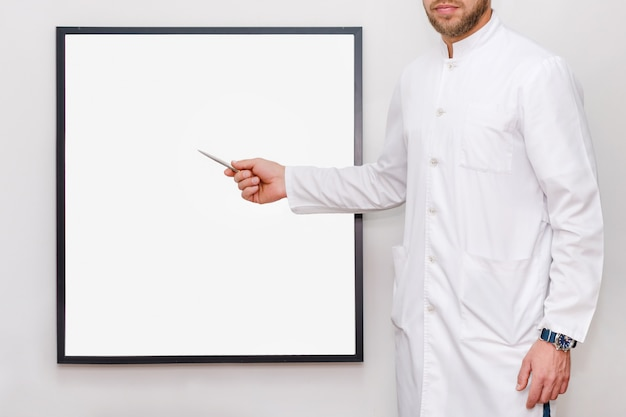 Homem de uniforme branco, apontando em uma moldura ou cartaz para mock-se. médico ou chef mostrando o quadro vazio, medicina, negócios e conceito de propaganda - homem com placa branca em branco