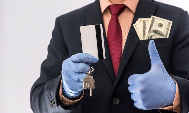 Homem de venda ou aluguel de segurança com luvas médicas contém a chave da casa e o dólar