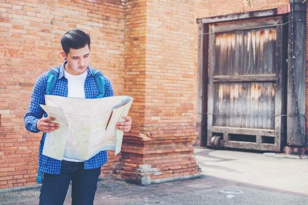 Homem de viagens na moda olhar procurando direção no mapa de localização