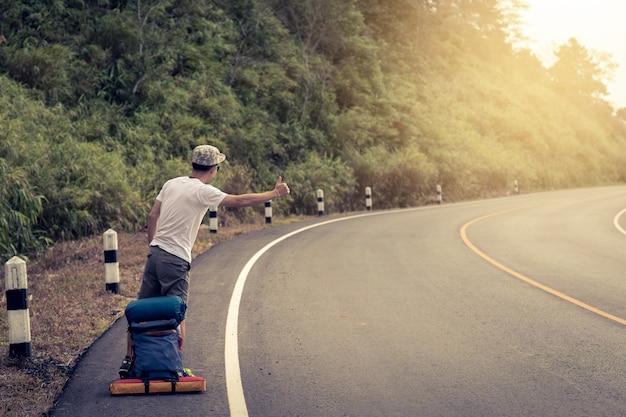 Homem de viagens pedindo carona. um caroneiro pela estrada durante a viagem de férias nas montanhas ao pôr do sol