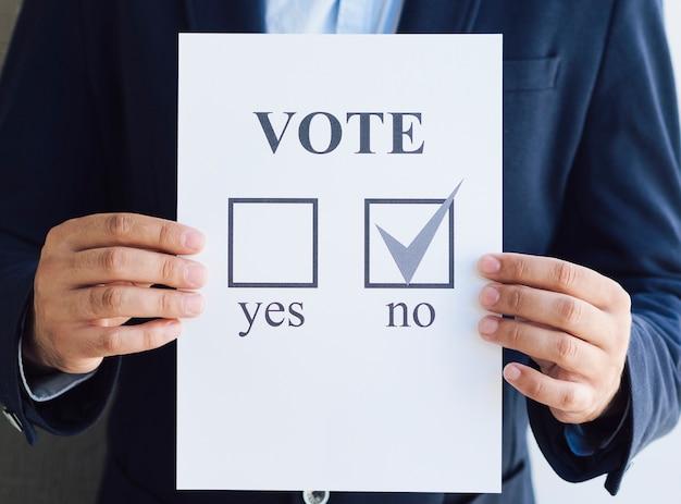 Homem de visão frontal, mostrando sua escolha negativa para o referendo