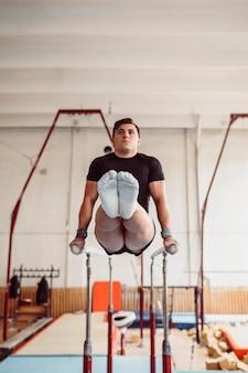 Homem de visão frontal se exercitando em barras paralelas