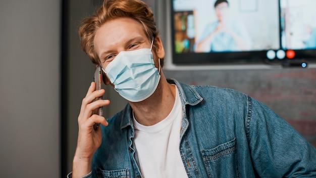 Homem de visão frontal usando máscara e falando ao telefone
