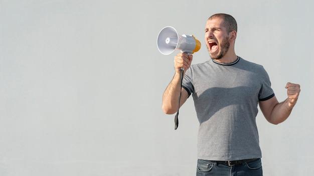 Homem de vista frontal com megafone gritando