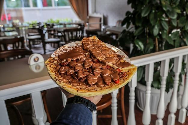 Homem de vista frontal segurando panquecas com frutas e chocolate voando em um prato