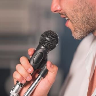 Homem de vista lateral cantando ao microfone