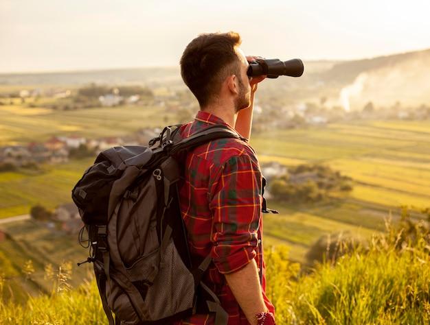 Homem de vista lateral com binóculo