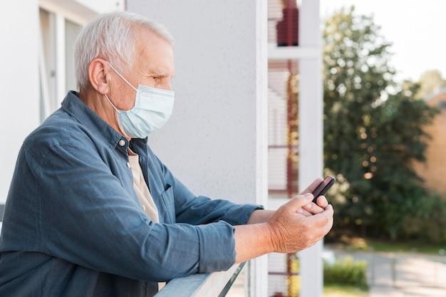Homem de vista lateral com telefone usando máscara