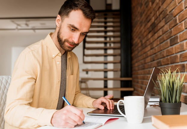 Homem de vista lateral fazendo videochamada no laptop e escrevendo