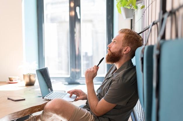 Homem de vista lateral pensando enquanto trabalha