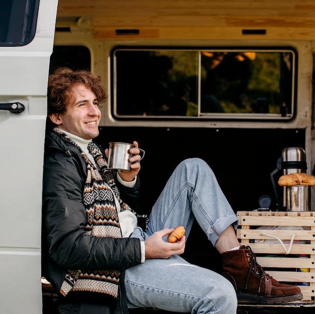 Homem de vista lateral sentado em uma van bebendo café