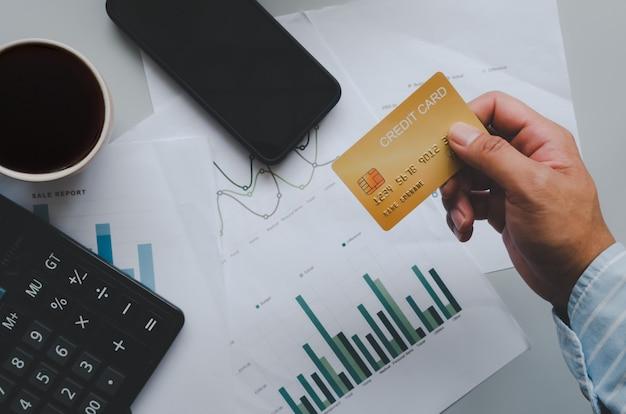 Homem de vista superior segurando um cartão de crédito e na mesa. calculadora de documentos de negócios e caneca de café e smartphone. negócio de compras online, pagamento com cartão de crédito.