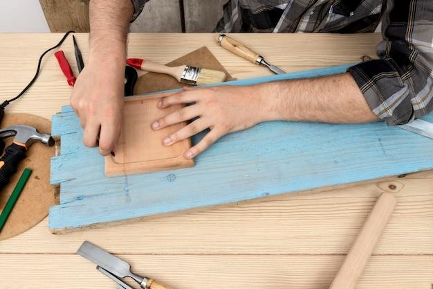 Homem de vista superior usando um lápis na madeira