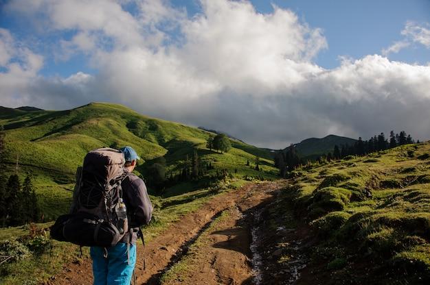 Homem de vista traseira andando na estrada de terra com caminhadas mochila e varas entre colinas
