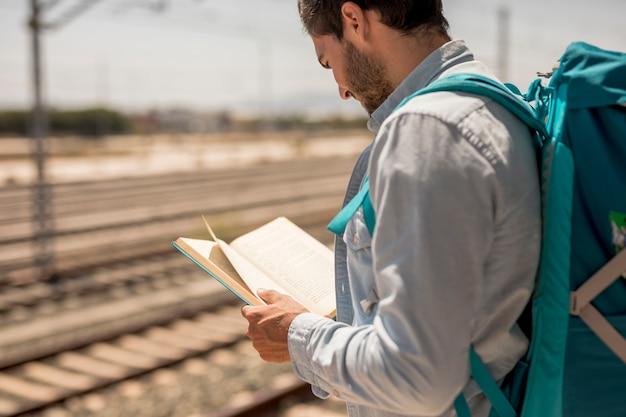 Homem de vista traseira, lendo um livro