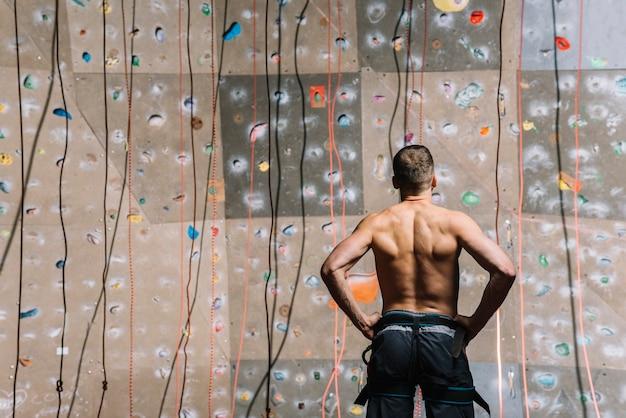 Homem de vista traseira olhando para parede de escalada