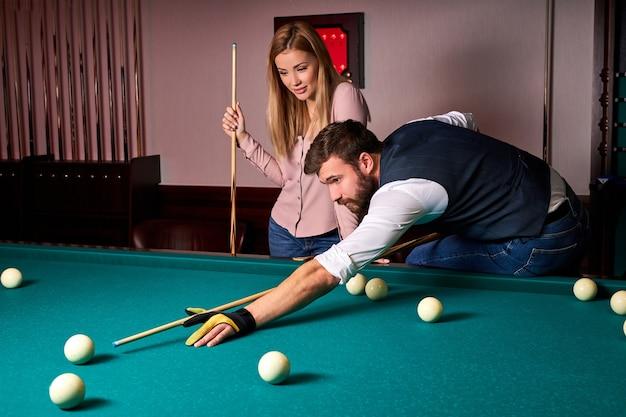 Homem debruçado sobre a mesa enquanto joga sinuca, ele se concentra no jogo, se divertindo com a namorada