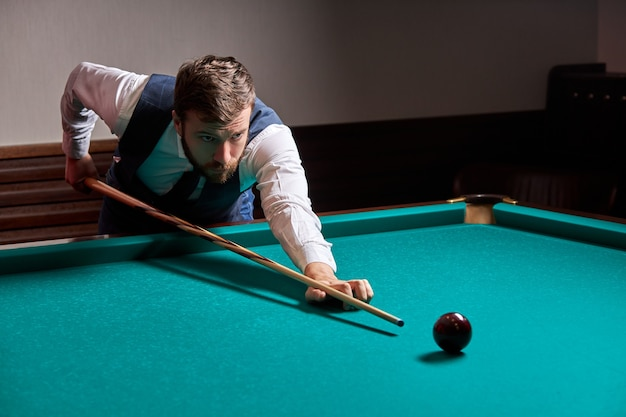 Homem debruçado sobre a mesa enquanto joga sinuca, ele se concentra no jogo, se divertindo