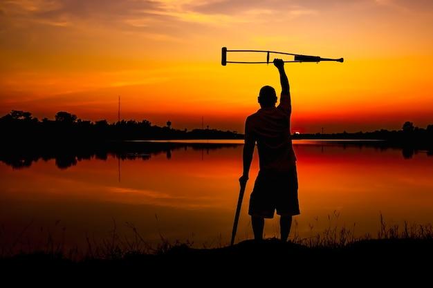 Homem deficiente com as muletas no fundo do nascer do sol.