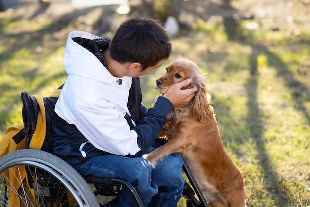 Homem deficiente com tiro médio acariciando cachorro