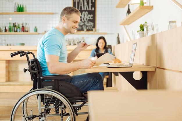 Homem deficiente de inspiração atraente, sentado em uma cadeira de rodas, segurando uma folha de papel, uma xícara de café e trabalhando em seu laptop