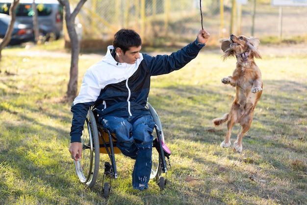 Homem deficiente de tiro completo brincando com cachorro