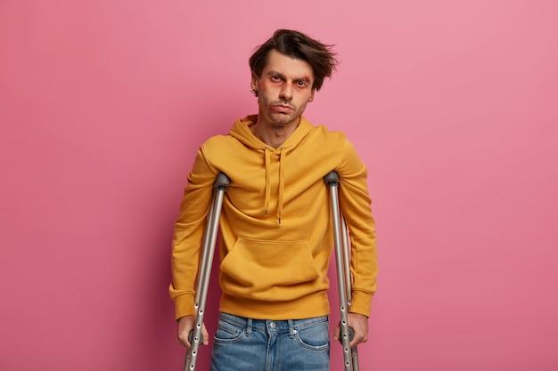 Homem deficiente ferido com hematomas, recupera-se de uma lesão, quebrou a perna