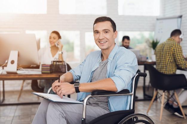 Homem deficiente na cadeira de rodas com a tabuleta no escritório.