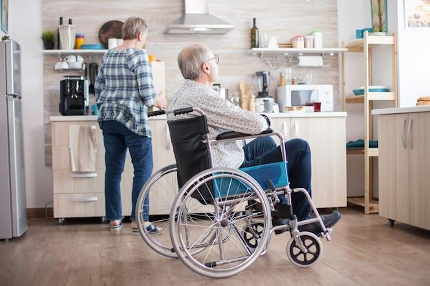 Homem deficiente pensativo em cadeira de rodas, olhando pela janela da cozinha enquanto a esposa desempacota a comida da sacola do supermercado. aposentado, paralisado, inválido, deficiente.