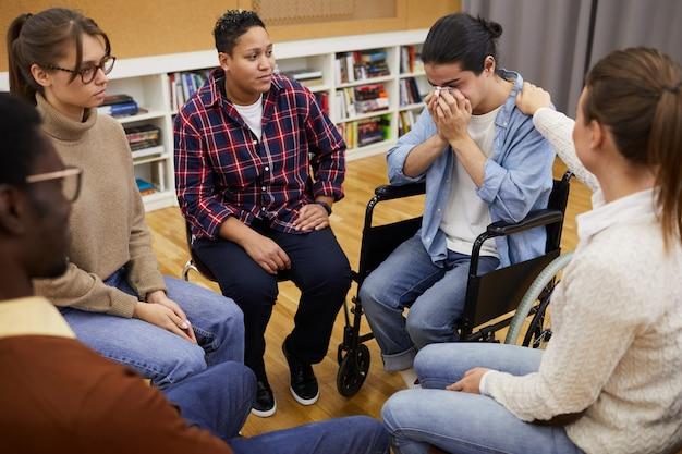 Homem deficiente que chora no grupo de apoio