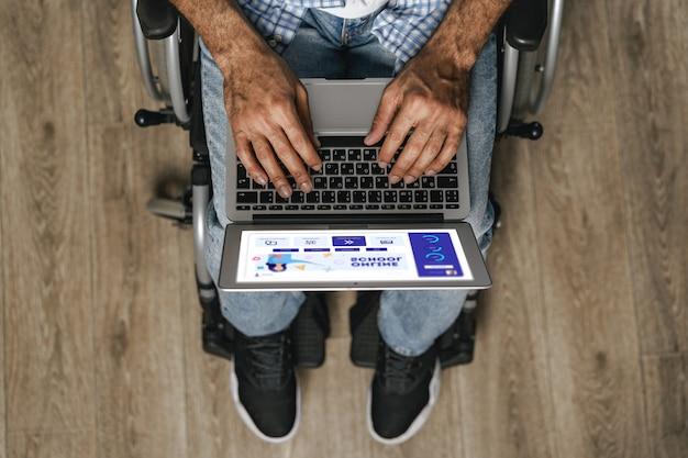 Homem deficiente sentado em uma cadeira de rodas e usando um laptop
