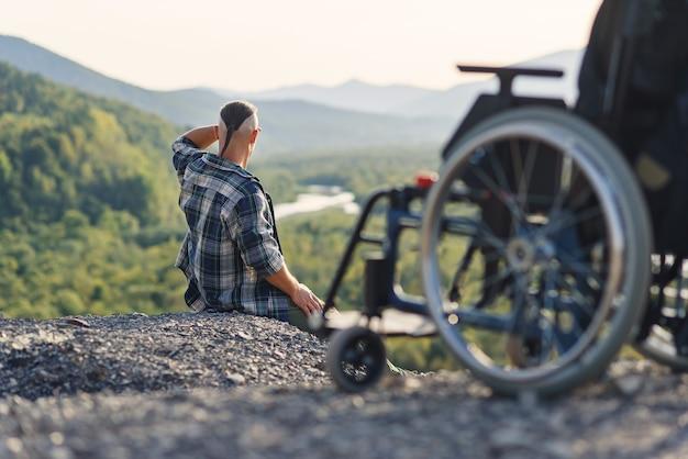 Homem deficiente sentado no topo de uma montanha perto de uma cadeira de rodas, curtindo a vida