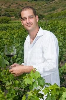 Homem degustando vinho de suas adegas em um vinhedo