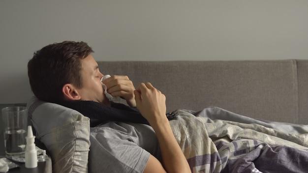 Homem deitado doente na cama ao lado de seus medicamentos em sua casa e assoando o nariz em um lenço