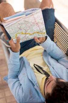 Homem deitado em um banco e olhando no mapa