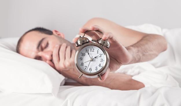Homem deitado na cama com despertador