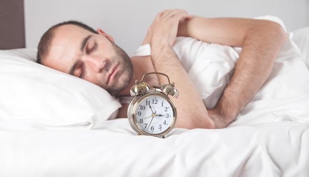 Homem deitado na cama com um despertador.